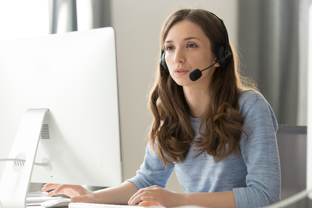 Foto de Serious young businesswoman in wireless headset call center agent telemarketer consulting client participating business video conference talk help as customer care service support helpline in office. - Imagen libre de derechos