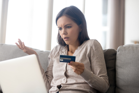 Photo pour Confused woman sitting on couch holds credit card use laptop looking at device screen having debt problems, transaction failed, money withdraw impossible, insecure online payment or scam fraud concept - image libre de droit