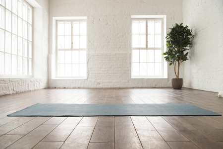 Photo for Unrolled yoga mat on wooden floor in modern fitness center or at home with big windows and white brick walls, comfortable space for doing sport exercises, meditating, yoga equipment - Royalty Free Image