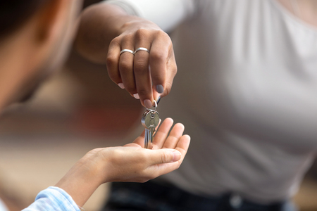 Photo pour Close up view of female realtor agent broker hand giving keys to new house to male customer renter buyer tenant owner making real estate deal buy flat property concept, mortgage investment contract - image libre de droit
