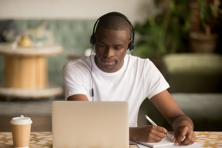 Photo pour Focused african man wearing headphones watching webinar training making notes study online learning language on computer, black male student looking at laptop elearning in internet write information - image libre de droit