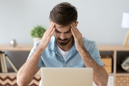 Foto de Tired man suffering from headache after long work with laptop, massaging temples, exhausted freelancer or student feeling pain or blood pressure, unwell, health problem concept, taking break - Imagen libre de derechos