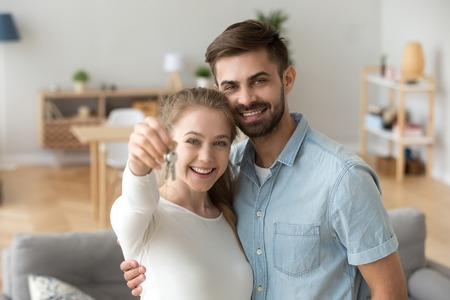 Photo pour Head shot portrait of happy couple in love holding keys, hugging, standing in living room in new house, looking at camera, satisfied clients posing for photo, wife and husband moving in own apartment - image libre de droit