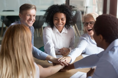 Photo pour Happy multi ethnic employees stacking hands in pile with coach mentor engaged in team building, multicultural office workers people group promise unity help loyalty teamwork at motivational training - image libre de droit