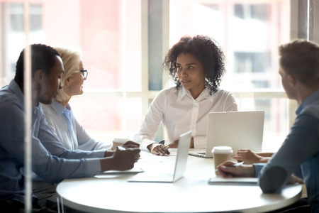Photo pour Serious african american female leader talking at diverse group boardroom meeting, multi-ethnic team people employees discussing deal benefits, negotiating on business contract terms with clients - image libre de droit