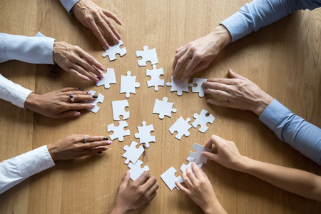 Photo pour Diverse business team people hands assemble puzzle together connect pieces at desk, employees collaborate find common solution engaged help contribute in effective teamwork concept top close up view - image libre de droit