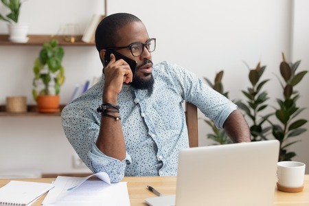 Foto de Serious african american businessman talking on the phone sitting at office desk with laptop, focused black manager making business call having mobile conversation on cellphone contacting client - Imagen libre de derechos