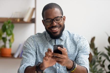 Foto de Happy african american businessman using phone mobile corporate apps at workplace texting sms, smiling black man looking at smartphone browsing internet, office technology and digital communication - Imagen libre de derechos