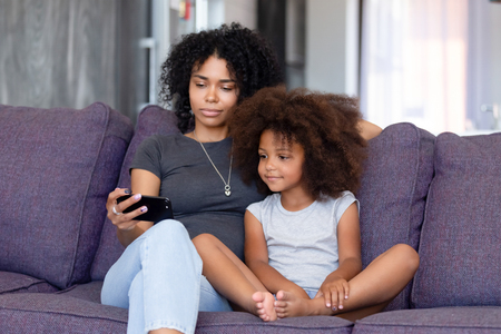 Foto de African American woman with daughter using phone together at home, sitting on sofa in living room, mother watching interesting cartoons with child, making selfie, video call, free time - Imagen libre de derechos