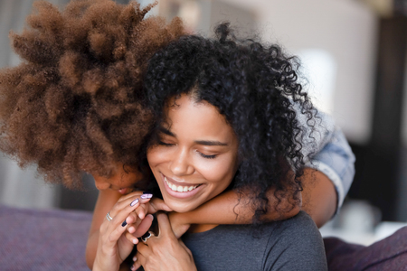 Foto de Close up smiling African American mother embracing with preschool daughter, sitting in living room on cozy sofa at home together, feeling happy, family warm relationships, showing support and love - Imagen libre de derechos