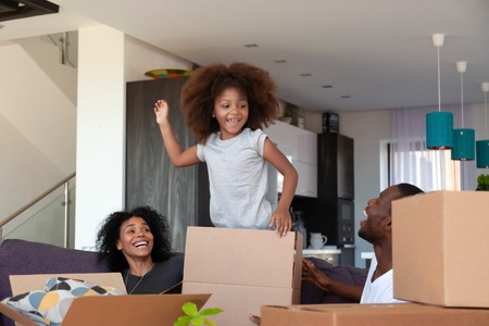 Photo pour Happy African American child and parents unpacking boxes in new house, having fun together on moving day, little smiling girl jumping on sofa in living room, family relocation concept - image libre de droit