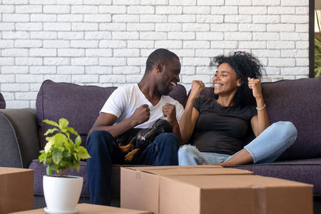 Photo pour Excited African American couple in love celebrating moving day, sitting together on sofa in living room in new house, handsome black man with dog at knees feeling happy about relocation - image libre de droit