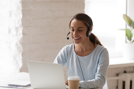 Photo pour Beautiful smiling woman working in headphones at office. Call center introduction. Happy employee at workplace. People at work at home. Video job interview, language course, class concept - image libre de droit