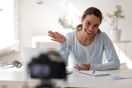 Photo pour Smiling beautiful woman waving hand looking at camera. Attractive female model posing, recording commercial news, promotional video, ads, advertising, tv show, live, reportage. Students making movie - image libre de droit