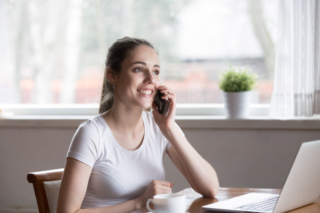 Photo pour Happy smiling woman talking over phone in morning at home. Millennial female speaking via smartphone near computer sitting. People working online, conversation, communication, technology concept - image libre de droit
