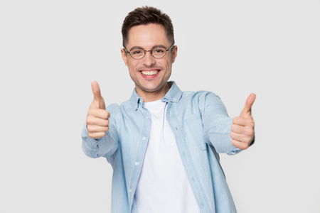 Photo pour Excited young Caucasian man student in glasses and shirt show thumbs up recommending service, happy male client in spectacles isolated on grey studio background give good positive recommendation - image libre de droit