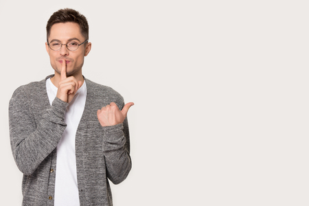 Photo pour Millennial Caucasian man in glasses show with finger black copy space for advertising, make hush gesture, young male isolated on grey studio background point on sale, do quiet shush sign, tell secret - image libre de droit