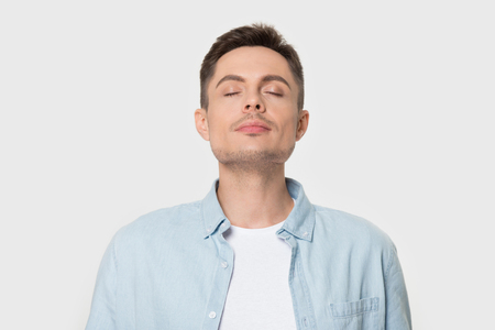 Photo pour Calm young Caucasian male isolated on grey studio background enjoy pleasant smell or fragrance, relaxed European man in shirt breath deep, feel mindful inhaling fresh air. Stress free concept - image libre de droit