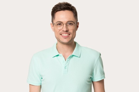 Foto de Headshot portrait of smiling millennial Caucasian man wearing glasses isolated on grey studio background, happy male in polo t-shirt and spectacles standing looking posing at camera - Imagen libre de derechos