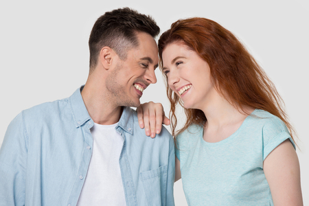 Photo pour Happy millennial man and woman laugh at funny joke have fun spend time together, smiling young couple or family isolated on grey studio background touch foreheads enjoy tender pleasant moment - image libre de droit