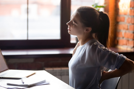 Foto de Side view young woman sitting at table working using computer take break touching massaging lower back feels discomfort after long sedentary studying, poor posture, incorrect stooped position concept - Imagen libre de derechos