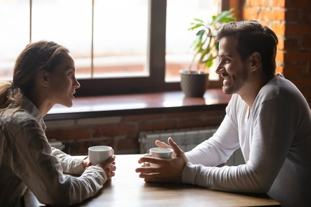Photo pour Side view smiling biracial woman sitting at table in cafe with caucasian man couple talking in cozy coffeeshop drinking tea coffee. Heterosexual friends romantic relationships or speed dating concept - image libre de droit