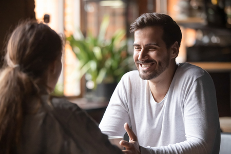 Photo pour Rear view woman sitting at table in cafe with handsome smiling man, people spends time at meeting searching for soul mate, male telling about himself making good first impression, speed dating concept - image libre de droit