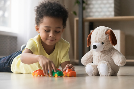 Mixed race adorable sweet toddler kid boy lying on warm heated wooden warm in modern home playroom playing with toy car and soft fluffy dog, children development and imagination creative games concept