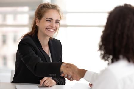 Foto de Happy businesswoman hr manager handshake hire candidate selling insurance services making good first impression, diverse broker and client customer shake hand at business office meeting job interview - Imagen libre de derechos