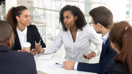 Photo pour Business team listening to african businesswoman coach speaking at training explaining corporate strategy, mixed race mentor talking at group meeting instructing employees consulting diverse clients - image libre de droit