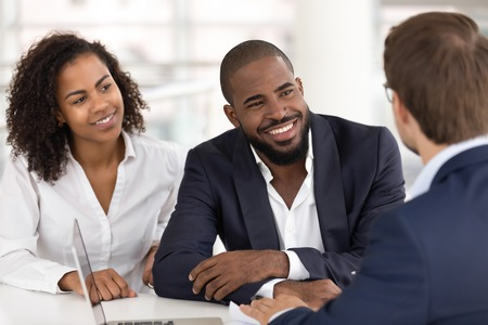 Happy african american young family couple listen to agent insurer salesman consulting black clients at meeting, bank manager agent talking to customers explaining insurance loan mortgage deal