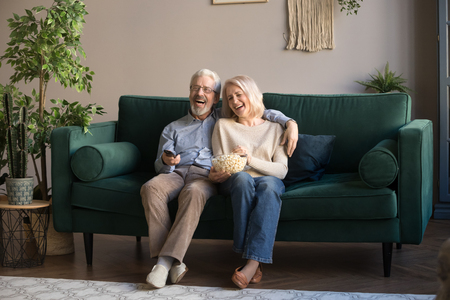 Foto de Happy aged couple, wife and husband watching tv, comedy movie and eating popcorn snack, laughing, sitting on cozy couch at home, mature family, man and woman enjoying free time, weekend together - Imagen libre de derechos