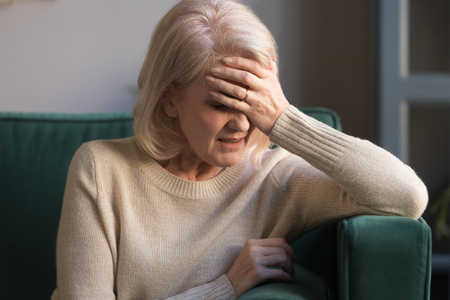 Foto de Unhappy mature grey haired woman suffering from headache, pain, touching forehead, panic attack, received bad news, depressed middle aged grandmother sitting on couch at home alone, close up - Imagen libre de derechos