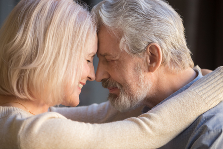Photo pour Romantic mature couple in love, wife and husband face to face, middle aged family enjoying tenderness and closeness, grey haired man and woman with closed eyes touching foreheads, close up - image libre de droit