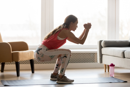 Photo for Side view young woman in activewear stands in sport mat do butt exercises deep static squat hold position improve body shape routine at home, healthy active lifestyle calories burn weight loss concept - Royalty Free Image
