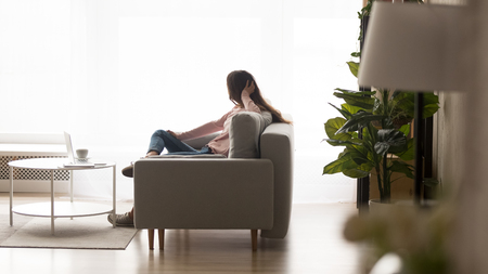 Photo pour Woman sitting on sofa lost on thoughts enjoy lazy day at home looking out the panoramic window, side view. Modern flat cozy living room interior with comfy couch, laminate flooring coffee table on rug - image libre de droit