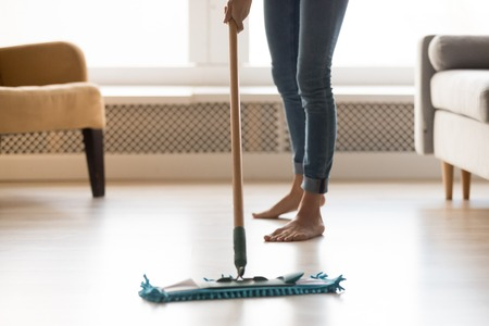 Foto de Close up cropped image of barefoot woman in casual clothes make house chores cleaning warm heated wooden laminate floor using wet mop, doing routine home work and housekeeping specialist job concept - Imagen libre de derechos