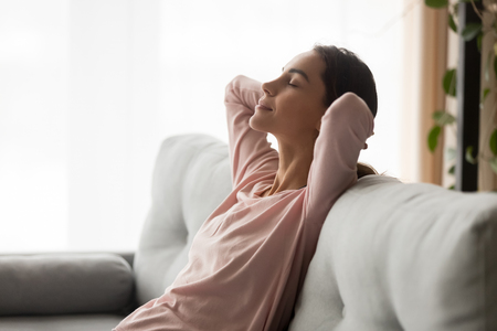 Photo pour Side close up view serene young woman holds hands behind head closed eyes feels placidity, tranquil girl having day nap leaning on comfortable sofa in living room, refreshment and daydreaming concept - image libre de droit