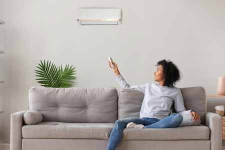 Photo for Smiling young African American woman using air conditioner, cooler system remote controller, switching, setting comfort temperature in living room, resting on cozy sofa at home, enjoy fresh air - Royalty Free Image