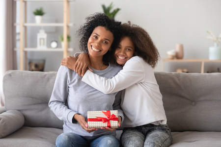 Foto de Head shot portrait of smiling African American mother received gift from teenage daughter, happy teen girl embracing mum holding box, posing for photo together, sitting on couch, looking at camera - Imagen libre de derechos