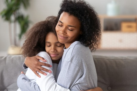 Foto de African American mother and teenage daughter embracing, enjoying moment together, sitting with closed eyes on couch at home, trusted relationships between mom and teen girl, showing love and care - Imagen libre de derechos