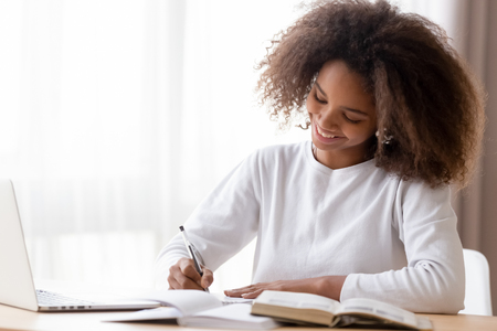 Foto de Smiling African American teen girl preparing school homework, using laptop, happy black schoolgirl, pupil doing tasks, writing essay, studying at home, making notes, writing, reading textbooks - Imagen libre de derechos