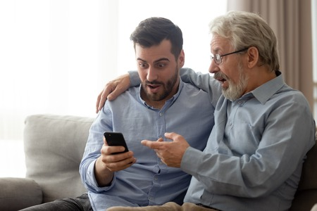 Photo for Millennial man and senior dad sit on couch at home feel surprised reading news on smartphone, amazed elderly father with grown son shocked by information or promotion using cellphone together - Royalty Free Image