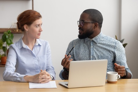 Photo pour Black african company member training candidate, sharing thoughts explaining idea with female coworker. Two diverse businesspeople sitting together in office. Coaching or brainstorming session concept - image libre de droit