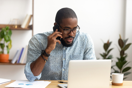 Foto de Serious african-american employee making business call focused on laptop at workplace. Black businessman consulting customer, discussing financial report. Contract negotiation and discussion concept - Imagen libre de derechos