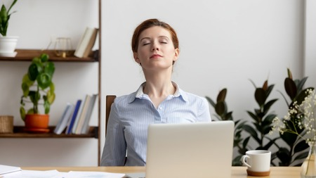 Foto de Businesswoman breathing, stretching shoulders after hard work feeling discomfort at office desk work. Young tired woman take minute pause keeping eyes closed. Uncomfortable chair, overwork on laptop - Imagen libre de derechos