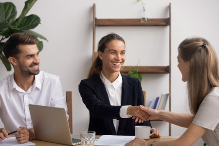 Photo pour Smiling female senior HR agent shaking hand congratulating candidate with successful start or end interview. Boss owner greeting newcomer or colleague with appointment in career or making deal - image libre de droit