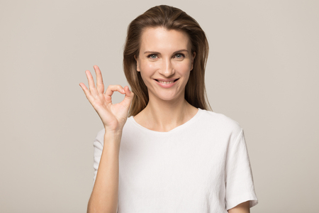 Foto de Beautiful young Caucasian woman isolated on grey studio background hold finger at lips ask be silent quiet, millennial female look at camera tell share mystery, announce secret sale or discount - Imagen libre de derechos