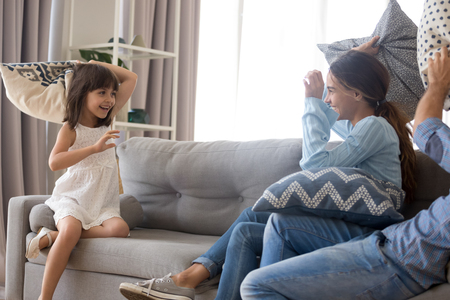 Photo pour Excited young family have fun at home engaged in pillow fight together, cute preschooler girl enjoy childish game with playful parents, mom and dad spend time entertaining with little daughter - image libre de droit