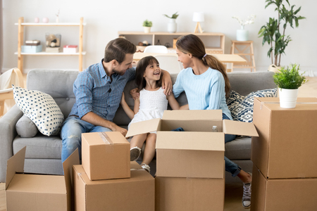 Photo pour Happy young parents sit on cozy couch with small smiling daughter relaxing on moving day, excited family have fun talking spend time together rest on sofa relocating to new house. Relocation concept - image libre de droit